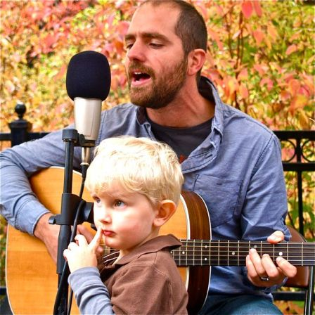 Levi Dean, here shown playing with his son in the foreground, will be on stage from 3:00-5:00 Sunday, June 9. Such a family affair at Lithia Artisans Market.