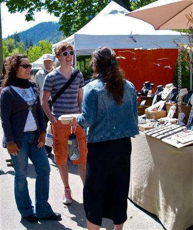 Happy customers enjoying the Lithia Artisans Market. Here in front of the Alma-Mia Jewelry by Karina Mendoza-Wittke.