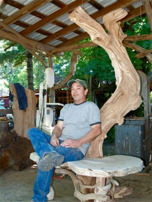 "Larry Shinerock in his outdoor workshop at ""It's A Burl"" wood gallery in Kirby, Oregon."