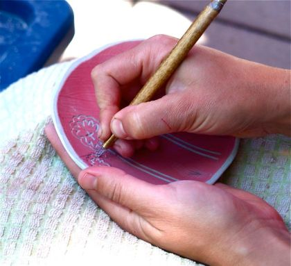 Lisa Eldredge, hands working clay with simple tools at the Lithia Artisans Market of Ashland Oregon.